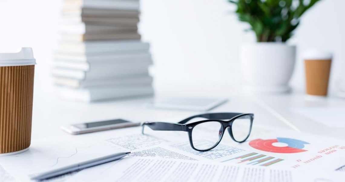 composition with eyeglasses and business documents on white desk