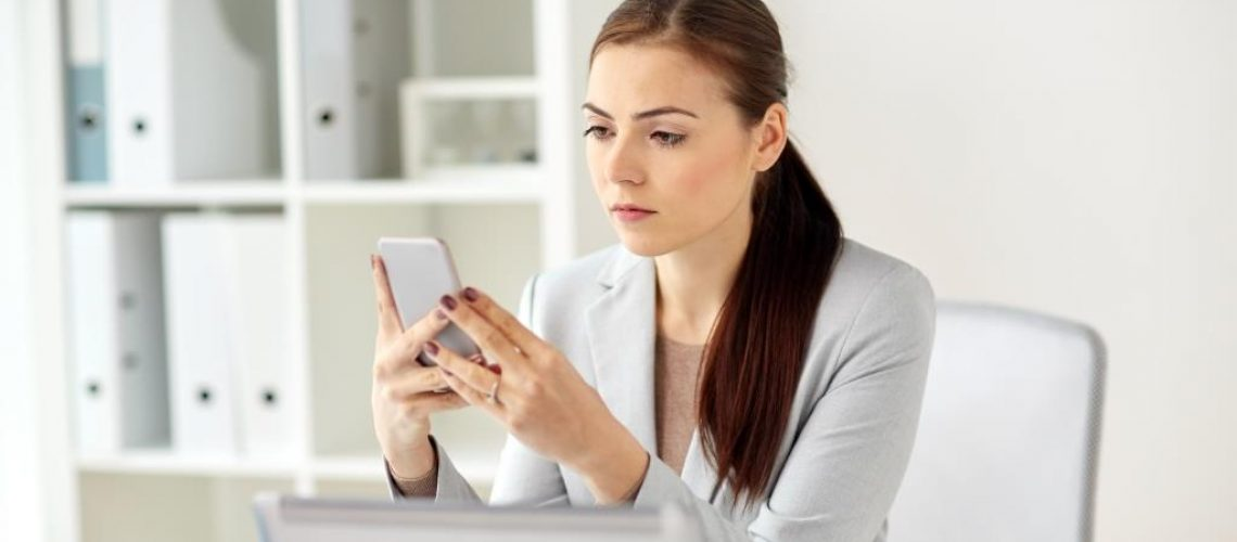 business, corporate, technology and people concept - businesswoman with smartphone at office