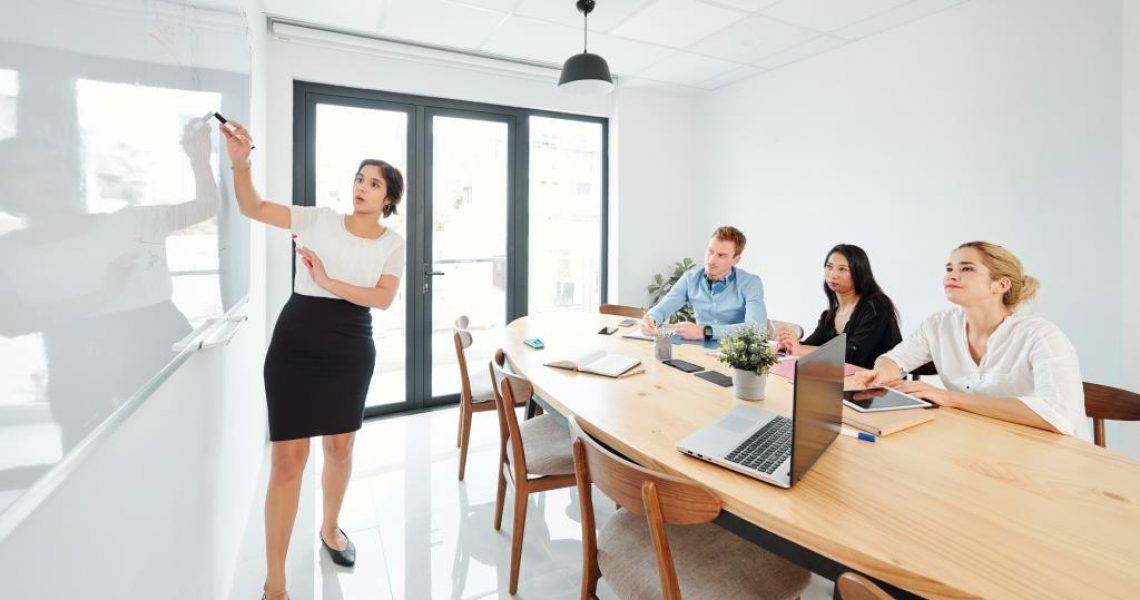 Young business trainer pointing at whiteboard and conducting business training for business people who sitting at the table and listening to her at office