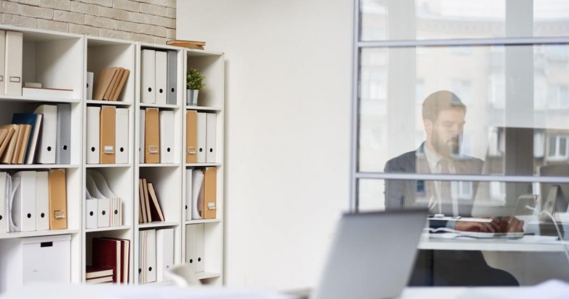 Background image of modern office space with blurred businessman working behind glass wall, copy space