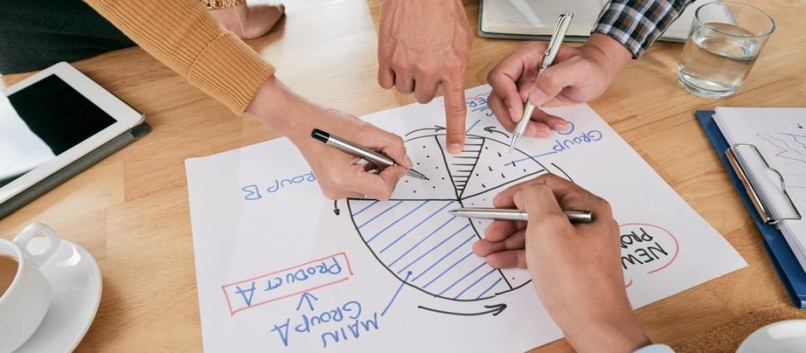 Hands of business people pointing at circle diagram