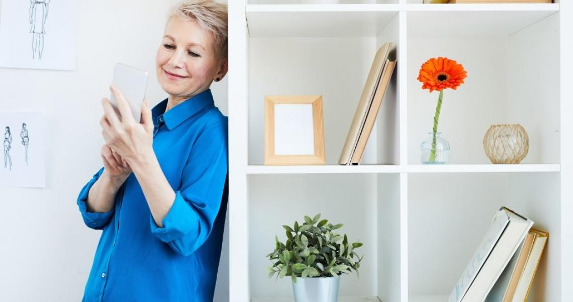 Happy mobile woman in blue shirt leaning by office furniture while making selfie or scrolling in smartphone at break
