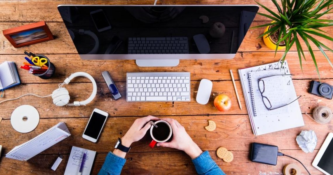 Business person working at office desk. Smart watch on hand and smart phone on the table. Holding a coffee cup. Notepad and eyeglasses and various office supplies around the workplace. Flat lay.