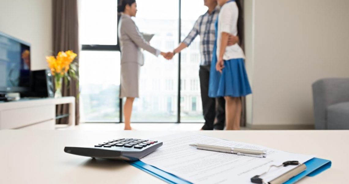 Close-up of pen, contract, calculator on the table and estate agent making a deal in the background