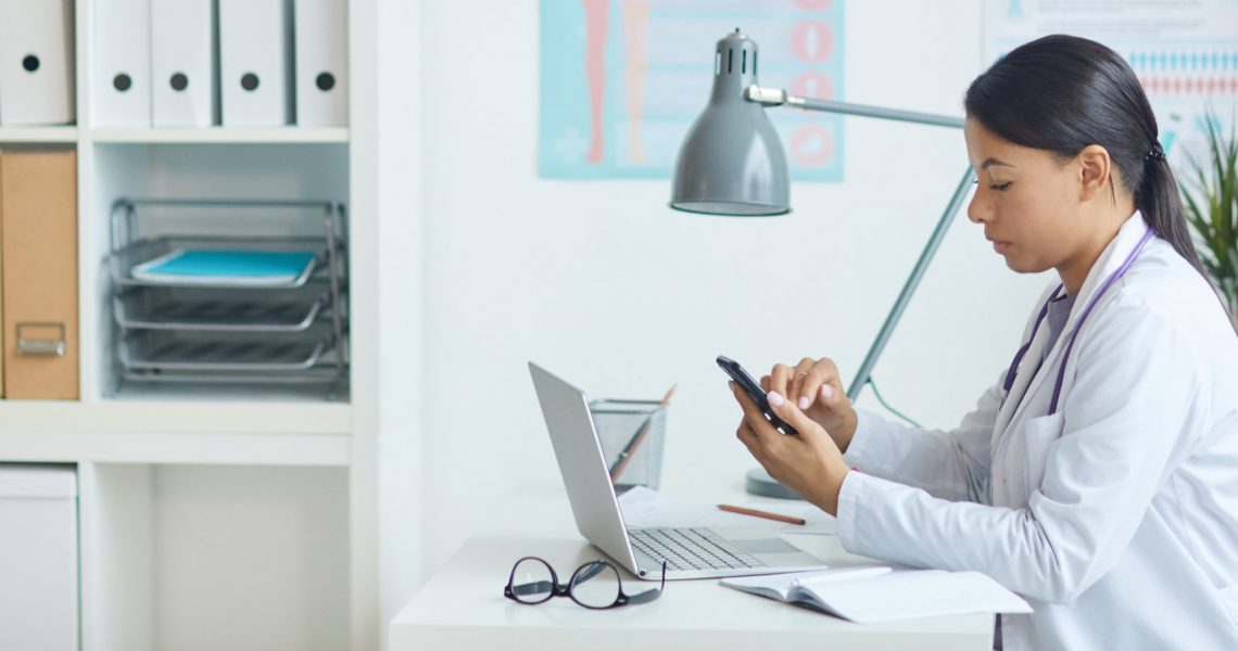 Young pediatrician sitting at her workplace in front of laptop and using mobile phone at office