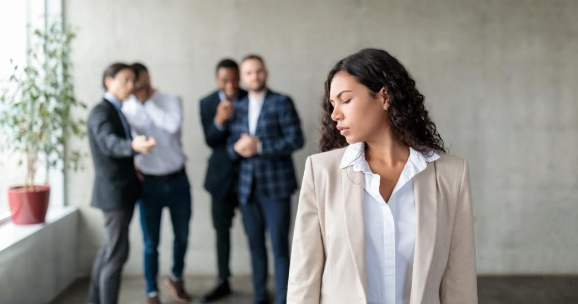 Sexism. Group Of Businessmen Whispering Behind Back Of Victimized Latin Businesswoman In Modern Office. Females Discrimination Problem, Workplace Bullying Concept. Panorama, Selective Focus